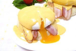 エッグベネディクトにナイフをいれ半熟卵が溢れている