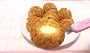 あまんちゅのクッキーシューをひとつ手に取り上部を開けて中のクリームが見えている