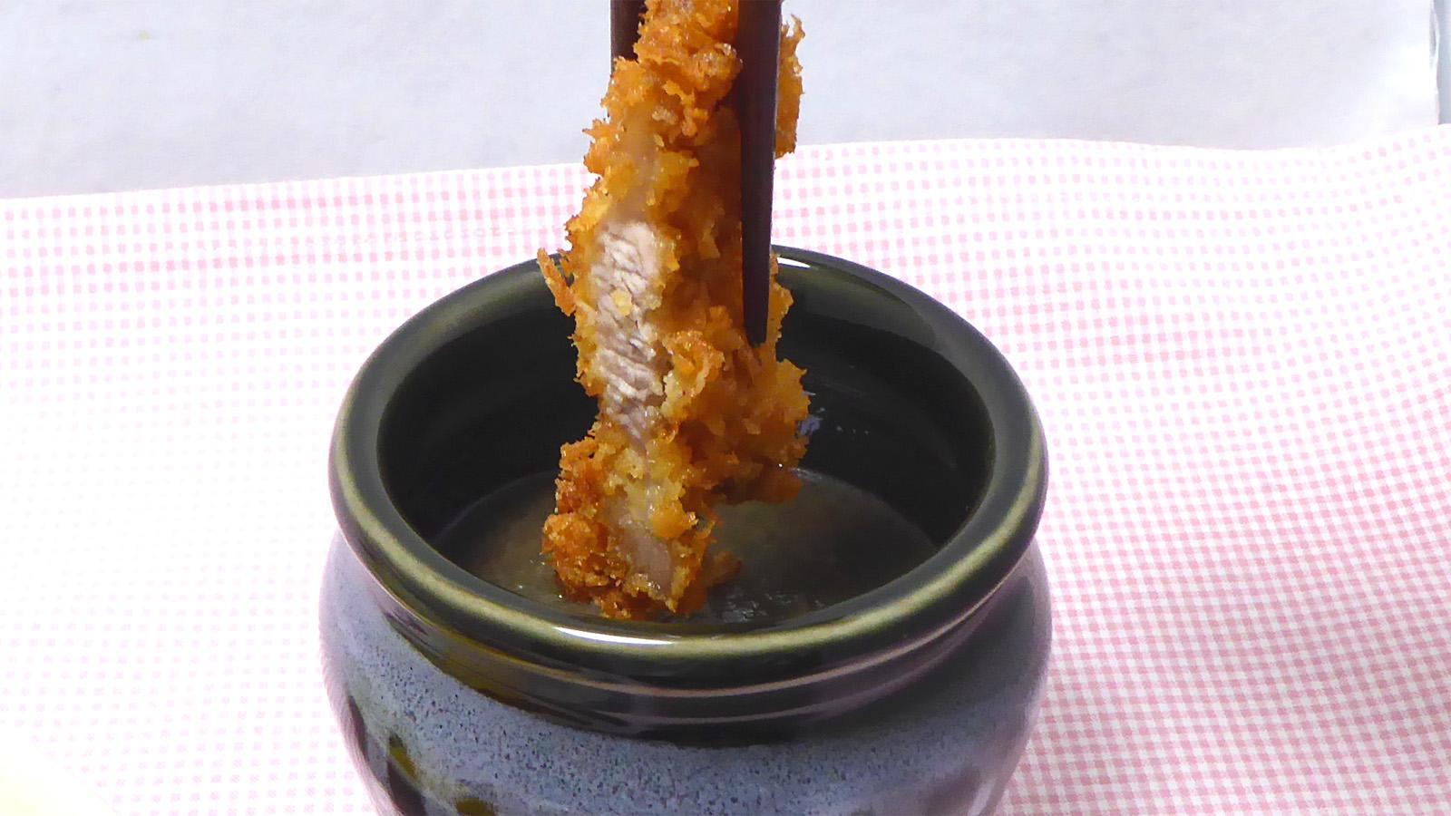 壺に入ったブラックチーズソースにロースカツを漬ける